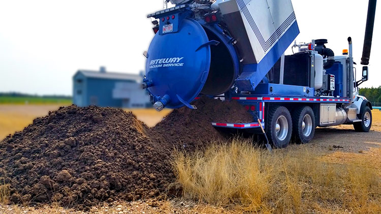 photo of an airvac truck dumping fresh dirt excavated from a project site in Alberta